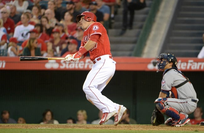 Jun 24, 2014; Anaheim, CA, USA; Los Angeles Angels center fielder Mike Trout (27) follows through on a two-run home run in the third inning as Minnesota Twins catcher Kurt Suzuki (8) watches at Angel Stadium of Anaheim. Mandatory Credit: Kirby Lee-USA TODAY Sports