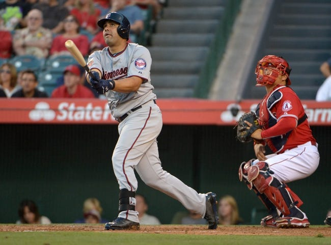 Jun 24, 2014; Anaheim, CA, USA; Minnesota Twins designated hitter Kendrys Morales (17) follows through on a solo home run in the second inning as Los Angeles Angels catcher Hang Conger (16) watches at Angel Stadium of Anaheim. Mandatory Credit: Kirby Lee-USA TODAY Sports