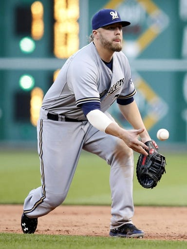 Jun 7, 2014; Pittsburgh, PA, USA; Milwaukee Brewers first baseman Mark Reynolds (7) flips the ball to first for a put out against the Pittsburgh Pirates during the ninth inning at PNC Park. The Brewers won 9-3. Mandatory Credit: Charles LeClaire-USA TODAY Sports