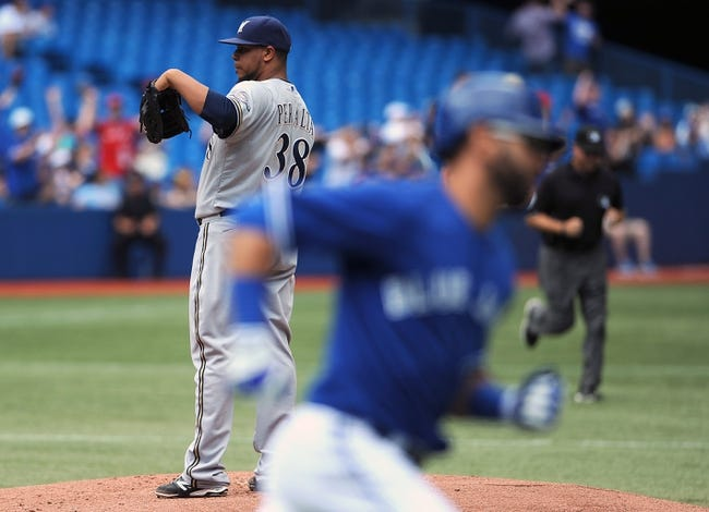 Jul 2, 2014; Toronto, Ontario, CAN;  Miilwaukee Brewers starting pitcher Wily Peralta waits for a new baseball as Toronto Blue Jays designated hitter Jose Bautista rounds first base after hitting a home run in the first inning at Rogers Centre. Mandatory Credit: Dan Hamilton-USA TODAY Sports