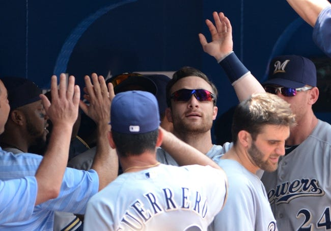 Jul 2, 2014; Toronto, Ontario, CAN;  Milwaukee Brewers first baseman Jonathan Lucroy is greeted in the dugout by team mates after scoring in the first inning against Toronto Blue Jays at Rogers Centre. Mandatory Credit: Dan Hamilton-USA TODAY Sports