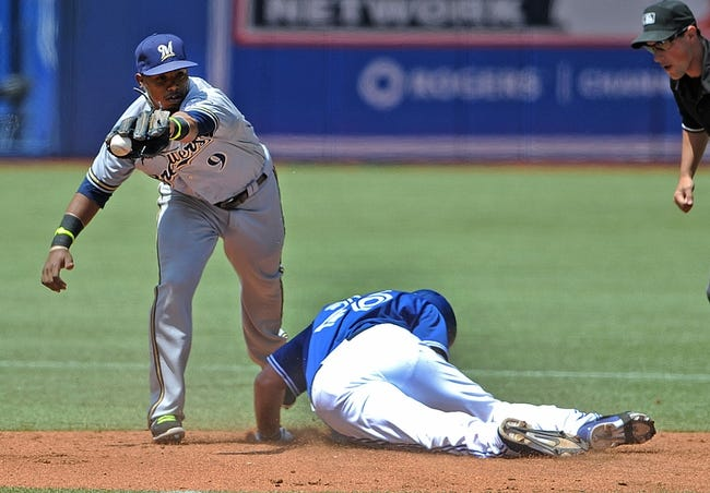 Jul 2, 2014; Toronto, Ontario, CAN; Milwaukee Brewers shortstop Jean Segura can't hang on to the ball as Toronto Blue Jays first baseman Adam Lind slides in safe at second with a double in the third inning  at Rogers Centre. Mandatory Credit: Dan Hamilton-USA TODAY Sports