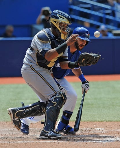 Jul 2, 2014; Toronto, Ontario, CAN;  Milwaukee Brewers catcher Martin Maldonado pushes past Toronto Blue Jays left fielder Darin Mastroianni as he fields a bunted ball to begin a double play in the seventh inning at Rogers Centre. Mandatory Credit: Dan Hamilton-USA TODAY Sports