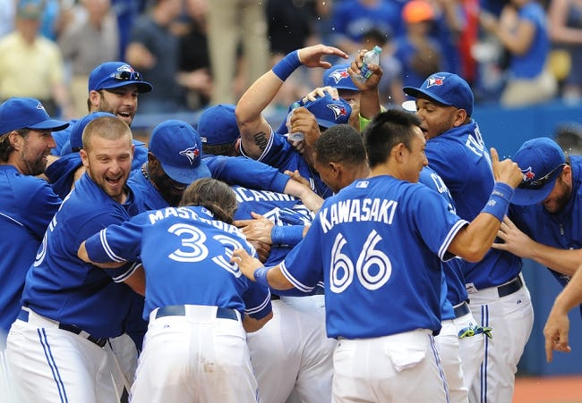 Jul 2, 2014; Toronto, Ontario, CAN; Toronto Blue Jays players celebrate with left fielder Edwin Encarnacion at home plate after his three-run home run in the bottom of the ninth gave them a 7-4 win over Milwaukee Brewers at Rogers Centre. Mandatory Credit: Dan Hamilton-USA TODAY Sports