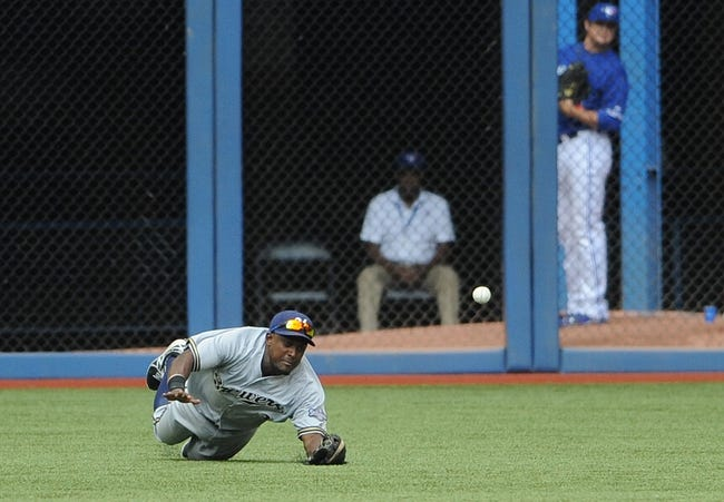 Jul 2, 2014; Toronto, Ontario, CAN;  Milwaukee Brewers left fielder Elian Herrera dives but misses a ball hit for a double by Toronto Blue Jays shortstop Jose Reyes (not pictured) in the ninth inning of the Jays 7-4 victory at Rogers Centre. Mandatory Credit: Dan Hamilton-USA TODAY Sports