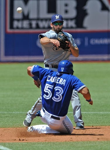 Jul 2, 2014; Toronto, Ontario, CAN;  Milwaukee Brewers second baseman Jeff Bianchi throws to first to complete a third inning double play after forcing out Toronto Blue Jaysright fielder Melky Cabrera in the Jays 7-4 win at Rogers Centre. Mandatory Credit: Dan Hamilton-USA TODAY Sports