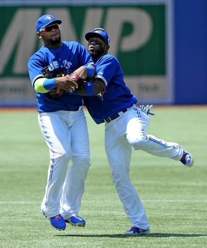 Jul 2, 2014; Toronto, Ontario, CAN;  Toronto Blue Jays shortstop Jose Reyes (right) collides with third baseman Juan Francisco after Francisco caught a pop up from Milwaukee Brewers  left fielder Elian Herrera (not pictured) in the seventh inning of the Jays 7-4 win at Rogers Centre. Mandatory Credit: Dan Hamilton-USA TODAY Sports