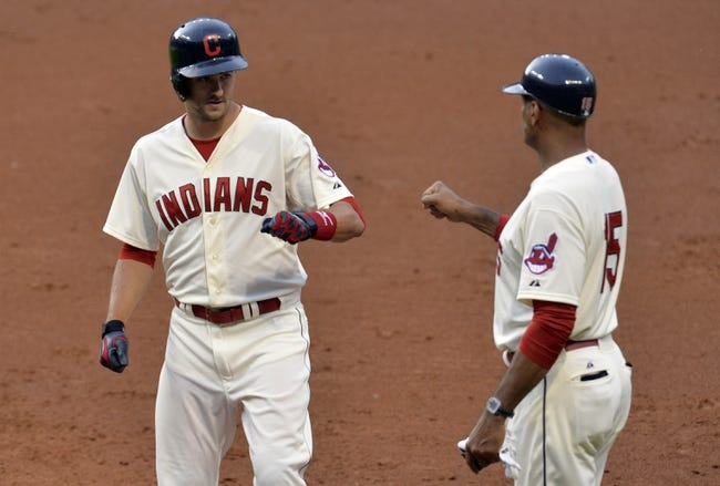 Jul 5, 2014; Cleveland, OH, USA; Cleveland Indians third baseman Lonnie Chisenhall (left) celebrates his RBI single with first base coach Sandy Alomar Jr. (15) in the third inning against the Kansas City Royals at Progressive Field. Mandatory Credit: David Richard-USA TODAY Sports