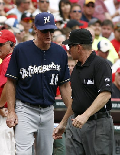 Jul 6, 2014; Cincinnati, OH, USA; Milwaukee Brewers manager Ron Roenicke (left) talks with first base umpire Jerry Meals  over a fan interference call  during the second inning against the Cincinnati Reds at Great American Ball Park. Mandatory Credit: David Kohl-USA TODAY Sports