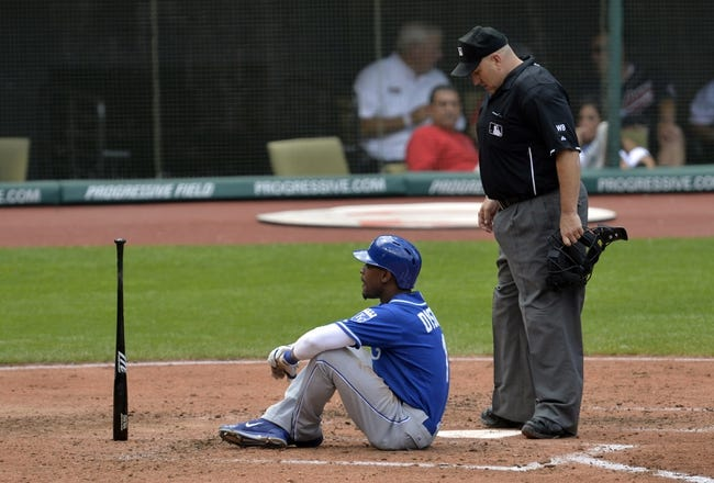 Jul 6, 2014; Cleveland, OH, USA; Home plate umpire Eric Cooper (right) reacts as Kansas City Royals center fielder Jarrod Dyson (1) sits at home plate after fouling off a pitch in the fifth inning against the Cleveland Indians at Progressive Field. Mandatory Credit: David Richard-USA TODAY Sports