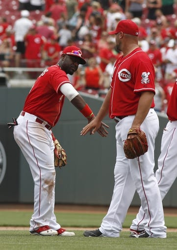 Jul 6, 2014; Cincinnati, OH, USA; Cincinnati Reds second baseman Brandon Phillips (4) congratulates relief pitcher Jonathan Broxton (51) after the Reds defeated the Milwaukee Brewers 4-2 at Great American Ball Park. Mandatory Credit: David Kohl-USA TODAY Sports