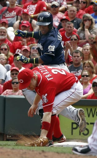 Jul 6, 2014; Cincinnati, OH, USA; Milwaukee Brewers shortstop Jean Segura (9) is forced out at first by Cincinnati Reds third baseman Todd Frazier (21) during the ninth inning at Great American Ball Park. The Reds won 4-2. Mandatory Credit: David Kohl-USA TODAY Sports