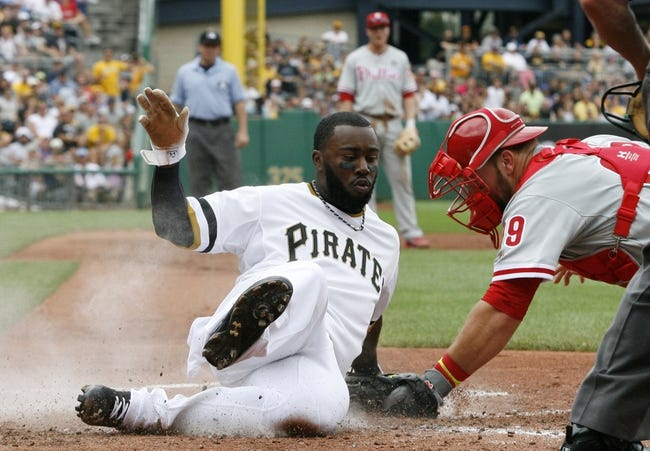 Jul 6, 2014; Pittsburgh, PA, USA; Pittsburgh Pirates left fielder Josh Harrison (5) slides home to score ahead of a tag by Philadelphia Phillies catcher Cameron Rupp (29) during the third inning at PNC Park. The Pirates won 6-2. Mandatory Credit: Charles LeClaire-USA TODAY Sports