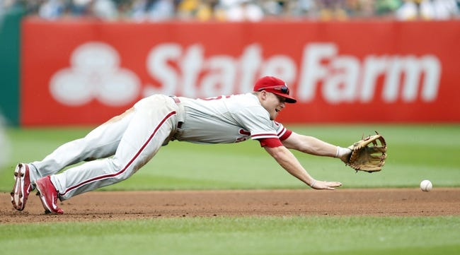 Jul 6, 2014; Pittsburgh, PA, USA; Philadelphia Phillies third baseman Cody Asche (25) reaches for a ball hit for a single by Pittsburgh Pirates shortstop Jordy Mercer (not pictured) during the seventh inning at PNC Park. The Pirates won 6-2. Mandatory Credit: Charles LeClaire-USA TODAY Sports