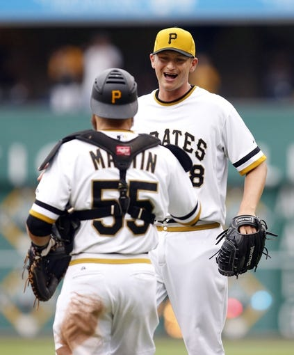 Jul 6, 2014; Pittsburgh, PA, USA; Pittsburgh Pirates relief pitcher Jared Hughes (48) celebrates with catcher Russell Martin (55) after defeating the Philadelphia Phillies at PNC Park. The Pirates won 6-2. Mandatory Credit: Charles LeClaire-USA TODAY Sports