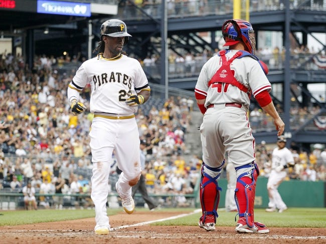 Jul 6, 2014; Pittsburgh, PA, USA; Pittsburgh Pirates center fielder Andrew McCutchen (22) scores behind Philadelphia Phillies catcher Koyie Hill (47) during the eighth inning at PNC Park. The Pirates won 6-2. Mandatory Credit: Charles LeClaire-USA TODAY Sports
