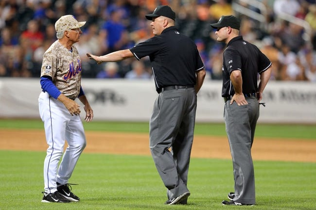 Jul 7, 2014; New York, NY, USA; New York Mets manager Terry Collins (10) challenges a call with umpires Mike Everitt (57) and Tim Timmons (95) during the ninth inning of a game against the Atlanta Braves at Citi Field. Mandatory Credit: Brad Penner-USA TODAY Sports