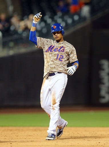 Jul 7, 2014; New York, NY, USA; New York Mets center fielder Juan Lagares (12) reacts after hitting a double against the Atlanta Braves during the eleventh inning of a game at Citi Field. The Mets defeated the Braves 4-3 in eleven innings. Mandatory Credit: Brad Penner-USA TODAY Sports