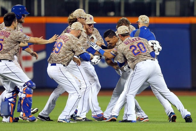 Jul 7, 2014; New York, NY, USA; New York Mets shortstop Ruben Tejada (11) is congratulated by teammates after his game-winning RBI single against the Atlanta Braves during the eleventh inning of a game at Citi Field. The Mets defeated the Braves 4-3 in eleven innings. Mandatory Credit: Brad Penner-USA TODAY Sports