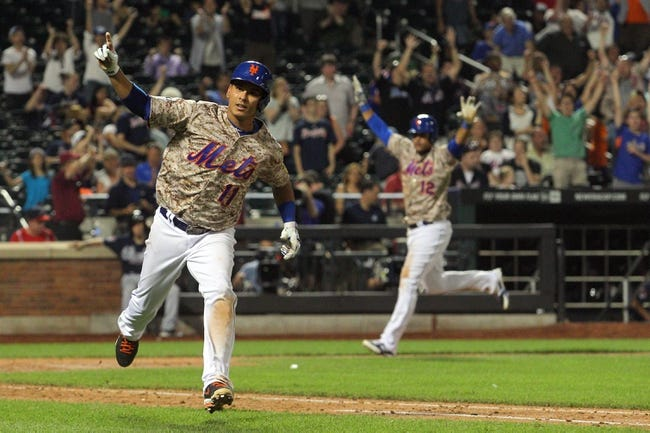 Jul 7, 2014; New York, NY, USA; New York Mets shortstop Ruben Tejada (11) and center fielder Juan Lagares (12) react after Tejada's game-winning RBI single against the Atlanta Braves during the eleventh inning of a game at Citi Field. The Mets defeated the Braves 4-3 in eleven innings. Mandatory Credit: Brad Penner-USA TODAY Sports