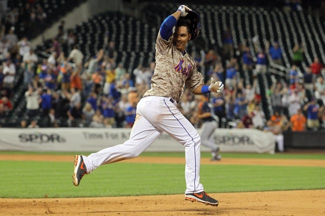 Jul 7, 2014; New York, NY, USA; New York Mets shortstop Ruben Tejada (11) tosses his helmet after his game-winning RBI single against the Atlanta Braves during the eleventh inning of a game at Citi Field. The Mets defeated the Braves 4-3 in eleven innings. Mandatory Credit: Brad Penner-USA TODAY Sports