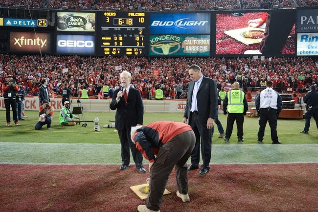 December 23, 2013; San Francisco, CA, USA; A Candlestick Park grounds keeper paints a yellow dot where former San Francisco 49ers wide receiver Dwight Clark (right) made his famous catch as sportscaster Joe Starkey (left) looks on during halftime in the final regular season game against the Atlanta Falcons at Candlestick Park. Mandatory Credit: Kyle Terada-USA TODAY Sports
