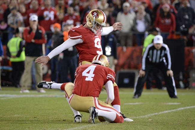 December 23, 2013; San Francisco, CA, USA; San Francisco 49ers kicker Phil Dawson (9) kicks the football out of the hold by punter Andy Lee (4) during the third quarter against the Atlanta Falcons in the final regular season game at Candlestick Park. The 49ers defeated the Falcons 34-24. Mandatory Credit: Kyle Terada-USA TODAY Sports