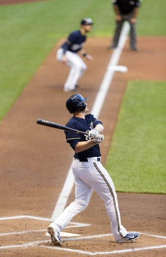 Jul 8, 2014; Milwaukee, WI, USA; Milwaukee Brewers first baseman Lyle Overbay (24) hits a grand slam home run as Milwaukee Brewers catcher Jonathan Lucroy (20) looks on from third base during the first inning against the Philadelphia Phillies at Miller Park. Mandatory Credit: Jeff Hanisch-USA TODAY Sports