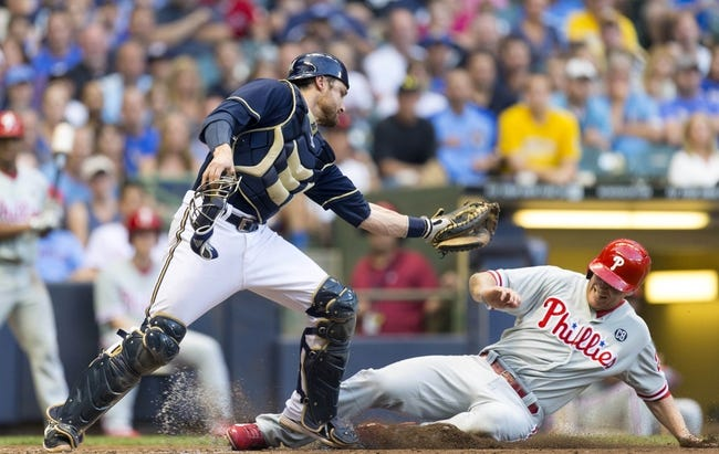 Jul 8, 2014; Milwaukee, WI, USA; Philadelphia Phillies third baseman Cody Asche (25) is out on a play at the plate as Milwaukee Brewers catcher Jonathan Lucroy (20) catches the throw during the first inning at Miller Park. Mandatory Credit: Jeff Hanisch-USA TODAY Sports