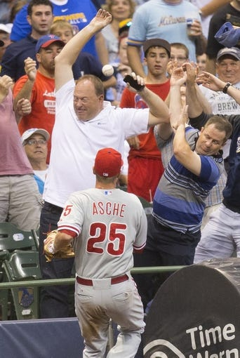 Jul 8, 2014; Milwaukee, WI, USA; Fans try to avoid a foul ball as Philadelphia Phillies third baseman Cody Asche (25) chases toward the stands during the fourth inning against the Milwaukee Brewers at Miller Park. Mandatory Credit: Jeff Hanisch-USA TODAY Sports