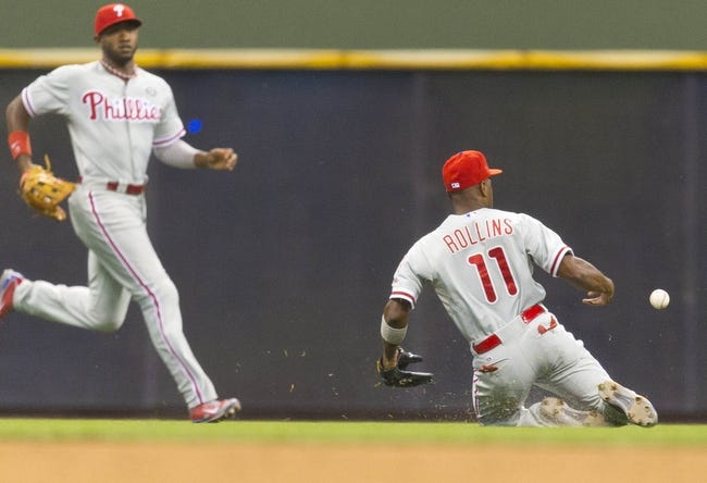 Jul 8, 2014; Milwaukee, WI, USA; Philadelphia Phillies shortstop Jimmy Rollins (11) and left fielder Domonic Brown (9) chase the ball hit by Milwaukee Brewers second baseman Scooter Gennett (2) (not pictured) during the sixth inning at Miller Park. Mandatory Credit: Jeff Hanisch-USA TODAY Sports