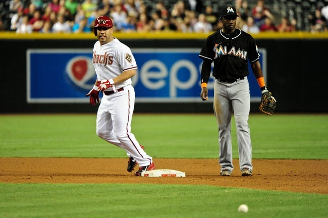 Jul 8, 2014; Phoenix, AZ, USA; Arizona Diamondbacks starting pitcher Vidal Nuno (54) and Miami Marlins shortstop Adeiny Hechavarria (3) watch as a bunt hit by center fielder Ender Inciarte (not pictured) sits on the grass during the fifth inning at Chase Field. Mandatory Credit: Matt Kartozian-USA TODAY Sports