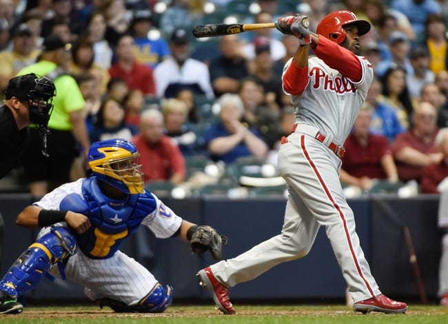 Jul 9, 2014; Milwaukee, WI, USA;  Philadelphia Phillies shortstop Jimmy Rollins (11) hits a two-run home run in the sixth inning as Milwaukee Brewers catcher Martin Maldonado (12) watches at Miller Park. Mandatory Credit: Benny Sieu-USA TODAY Sports