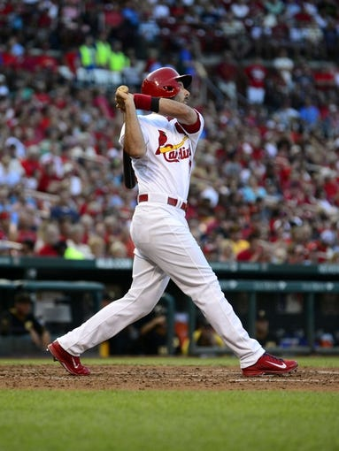 Jul 10, 2014; St. Louis, MO, USA; St. Louis Cardinals third baseman Matt Carpenter (13) hits a sacrifice fly off of Pittsburgh Pirates starting pitcher Edinson Volquez (not pictured) during the third inning at Busch Stadium. Mandatory Credit: Jeff Curry-USA TODAY Sports