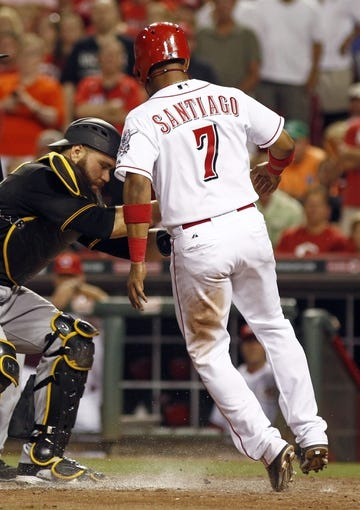 Jul 11, 2014; Cincinnati, OH, USA; Cincinnati Reds shortstop Ramon Santiago (7) is tagged out by Pittsburgh Pirates catcher Russell Martin in the eighth inning at Great American Ball Park. The Reds won 6-5. Mandatory Credit: David Kohl-USA TODAY Sports