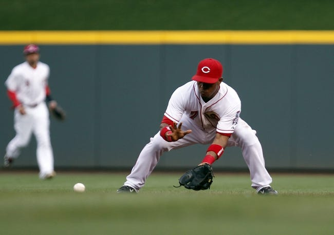 Jul 12, 2014; Cincinnati, OH, USA; Cincinnati Reds shortstop Ramon Santiago (7) makes a play during the third inning against the Pittsburgh Pirates at Great American Ball Park. Mandatory Credit: Frank Victores-USA TODAY Sports