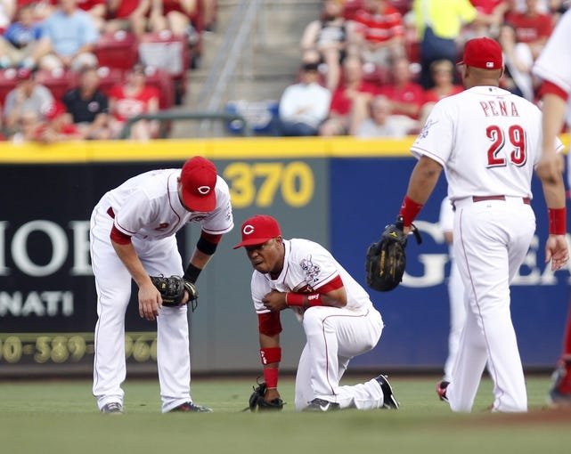 Jul 12, 2014; Cincinnati, OH, USA; Cincinnati Reds shortstop Ramon Santiago (7) is looked at by shortstop Zack Cozart (2) and catcher Brayan Pena (29) after injuring his shoulder during the first inning against the Pittsburgh Pirates at Great American Ball Park. Mandatory Credit: Frank Victores-USA TODAY Sports