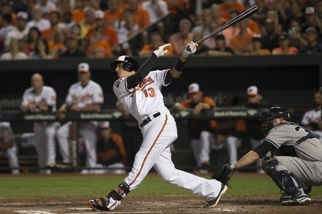 Jul 13, 2014; Baltimore, MD, USA; Baltimore Orioles third baseman Manny Machado (13) hits a single during the second inning against the New York Yankees at Oriole Park at Camden Yards. Mandatory Credit: Tommy Gilligan-USA TODAY Sports