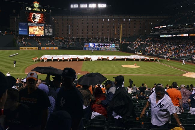Jul 13, 2014; Baltimore, MD, USA; The grounds crew races to put the tarp on the field during the bottom of the fifth inning of the game between the New York Yankees and Baltimore Orioles  at Oriole Park at Camden Yards. Mandatory Credit: Tommy Gilligan-USA TODAY Sports