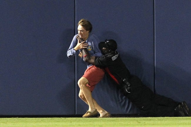 Jul 18, 2014; Atlanta, GA, USA; A security guard tackles a fan that ran onto the field during the ninth inning of the game between the Atlanta Braves and Philadelphia Phillies at Turner Field. The Braves defeated the Phillies 6-4.  Mandatory Credit: Brett Davis-USA TODAY Sports