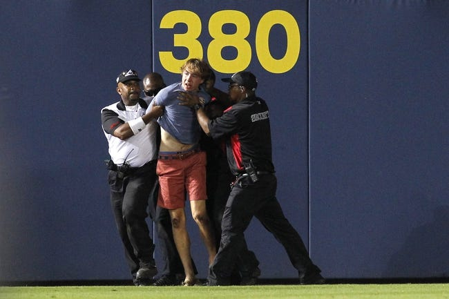 Jul 18, 2014; Atlanta, GA, USA; Security guards tackle a fan that ran onto the field during the ninth inning of the game between the Atlanta Braves and Philadelphia Phillies at Turner Field. The Braves defeated the Phillies 6-4.  Mandatory Credit: Brett Davis-USA TODAY Sports