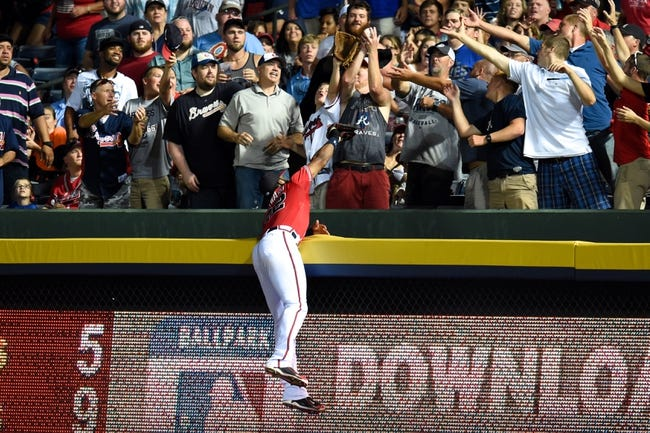 Jul 19, 2014; Atlanta, GA, USA; A fan catches Philadelphia Phillies shortstop Jimmy Rollins (11) (not shown) home run above a leaping Atlanta Braves right fielder Jason Heyward (22) during the seventh inning at Turner Field. Mandatory Credit: Dale Zanine-USA TODAY Sports