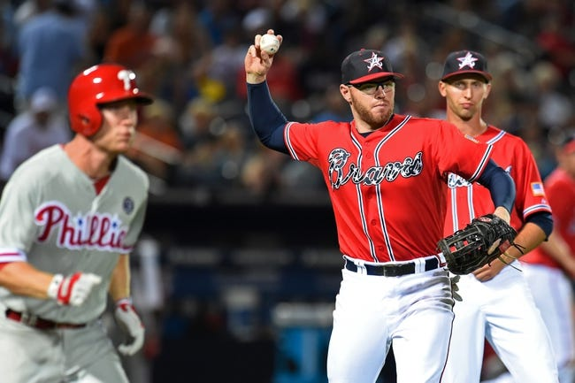 Jul 19, 2014; Atlanta, GA, USA; Atlanta Braves first baseman Freddie Freeman (5) throws out Philadelphia Phillies third baseman Cody Asche (25) (left) after a sacrifice during the eighth inning at Turner Field. The Phillies defeated the Braves 2-1. Mandatory Credit: Dale Zanine-USA TODAY Sports