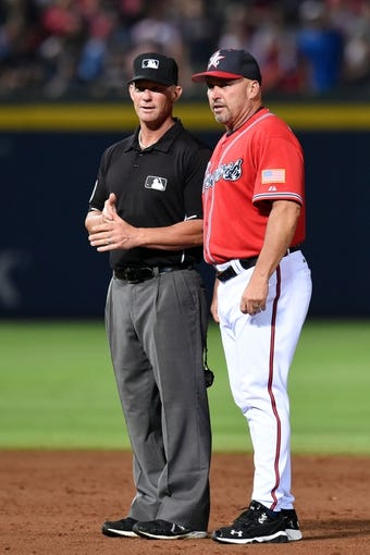 Jul 19, 2014; Atlanta, GA, USA; Atlanta Braves manager Fredi Gonzalez (33) discusses a call with MLB umpire Jim Wolf (28) during the game against the Philadelphia Phillies during the eighth inning at Turner Field. The Phillies defeated the Braves 2-1. Mandatory Credit: Dale Zanine-USA TODAY Sports