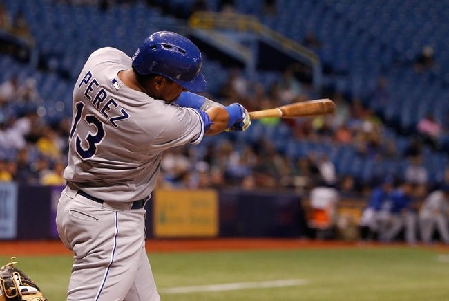 Jul 8, 2014; St. Petersburg, FL, USA; Kansas City Royals catcher Salvador Perez (13) hits a 2-RBI single during the ninth inning against the Tampa Bay Rays at Tropicana Field. Tampa Bay Rays defeated the Kansas City Royals 4-3. Mandatory Credit: Kim Klement-USA TODAY Sports