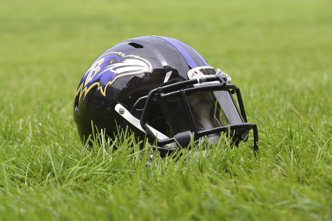 Jul 24, 2014; Owings Mills, MD, USA;  A detailed view of an Baltimore Ravens helmet  in the grass after practice at Under Armour Performance Center. Mandatory Credit: Tommy Gilligan-USA TODAY Sports