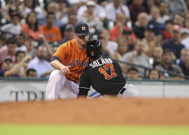 Jul 25, 2014; Houston, TX, USA; Miami Marlins second baseman Donovan Solano (17) is out at third base on an attempted stolen base during the fourth inning as Houston Astros third baseman Matt Dominguez (30) applies the tag at Minute Maid Park. Mandatory Credit: Troy Taormina-USA TODAY Sports