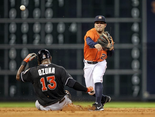 Jul 25, 2014; Houston, TX, USA; Houston Astros second baseman Jose Altuve (27) throws to first base to complete a double play during the fifth inning as Miami Marlins center fielder Marcell Ozuna (13) is out at second base at Minute Maid Park. Mandatory Credit: Troy Taormina-USA TODAY Sports