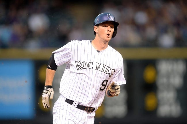 Jul 25, 2014; Denver, CO, USA; Colorado Rockies second basemen D.J. LeMahieu runs to third after a triple in the third inning against the Pittsburgh Pirates at Coors Field. Mandatory Credit: Ron Chenoy-USA TODAY Sports