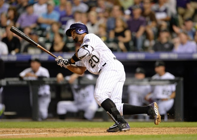 Jul 25, 2014; Denver, CO, USA; Colorado Rockies catcher Wilin Rosario (20) hits a RBI double in the seventh inning against the Pittsburgh Pirates at Coors Field. Mandatory Credit: Ron Chenoy-USA TODAY Sports